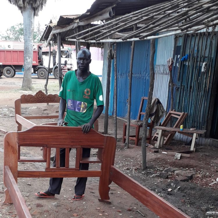 A South Sudanese man building bed frames to sell